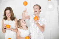 Mother and daughter studding oranges with cloves while son juggling with oranges 11077004427| 写真素材・ストックフォト・画像・イラスト素材|アマナイメージズ