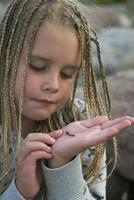 Girl holding bug on palm, close-up