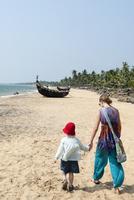Teenage girl walking with younger sister on beach 11077005788| 写真素材・ストックフォト・画像・イラスト素材|アマナイメージズ