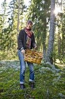 Smiling mature woman with basket full of mushrooms