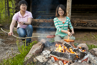 Two female tourists roasting sages in fire