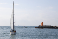 Sailing boat on sea, lighthouse in background