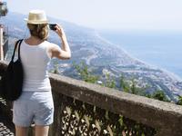 Woman taking picture of coastline 11077007303| 写真素材・ストックフォト・画像・イラスト素材|アマナイメージズ