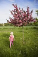 Girl running near flowering apple tree