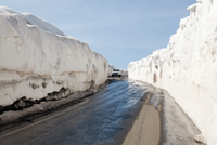 Car on country road with snowdrifts on sides