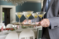 Man carrying tray with dry martini cocktails