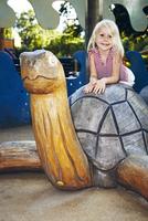 Girl on wooden tortoise
