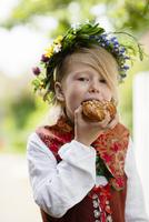 Girl in national costume eating cinnamon bun