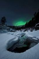 Aurora Borealis over Tennevik River in Norway.
