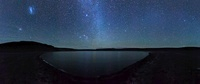 A panoramic view of the Milky Way and La Azul lagoon in Somu