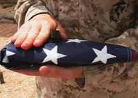 A soldier holds the United States flag.