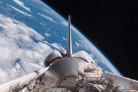 Space Shuttle Discovery backdropped by Earth.