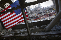 The American Flag is prominent amongst the rubble of what wa