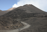 Hikers walking towards summit area of Mount Etna volcano, Sicily, Italy.
