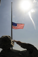 An Airman salutes the American flag that is flying at half-mast.