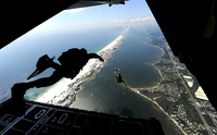 U.S. Airmen jump out of a C-130 Hercules.