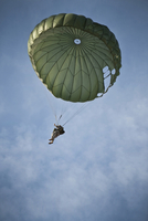 An Airman descends through the sky with parachute deployed.