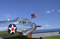 A BT-13 Valiant trainer aircraft with American Flag.