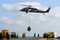 An MH-60S Sea Hawk helicopter lowers pallets of supplies onto USS Bonhomme Richard.