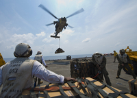 An MH-60s Sea Hawk helicopter lowers cargo to the flight deck of USS Bonhomme Richard.
