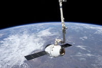 The SpaceX Dragon cargo craft in the grasp of the Canadarm2.