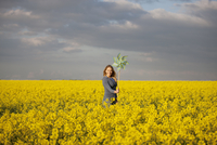 A young woman standing in a rape seed field holding a windmi 11080002991| 写真素材・ストックフォト・画像・イラスト素材|アマナイメージズ