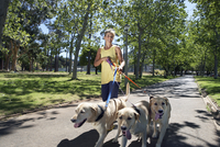 Woman taking three dogs for walk in park, smiling
