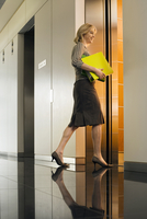 Businesswoman entering office elevator, carrying folders, smiling, side view, surface level