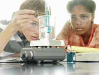 Teenage boy and girl (15-17) doing science experiment at desk in classroom, surface level