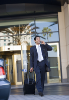 Businessman leaving hotel with luggage in tow, using mobile phone, smiling