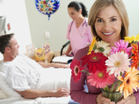 Male patient lying in hospital bed, talking to nurse, focus on female visitor holding flowers, smiling, portrait