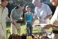 Three generation family standing beside barbecue grill in garden, senior man serving granddaughter (11-13) sausage, smiling