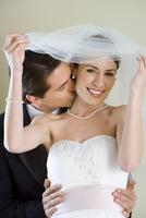 Groom standing behind bride at wedding, kissing her on cheek, bride removing veil, smiling, portrait