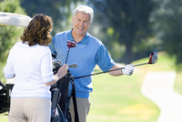 Mature couple playing golf, man in blue tank top taking driver from golf bag, smiling