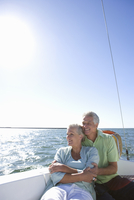 Mature couple sitting on deck of yacht out at sea, woman leaning contentedly against man, looking at view (backlit)