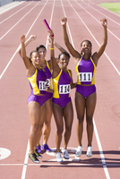 Team of female athletes cheering relay race victory