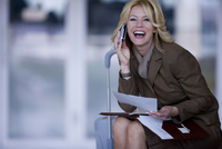 Businesswoman with suitcase talking on cell phone