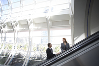 Business people using escalator in airport