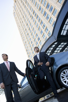 Chauffeur holding door for businessman