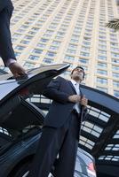 Businessman exiting car in urban setting