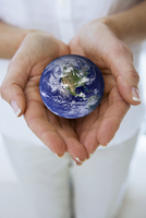 Close up of woman窶冱 hands cupping miniature globe