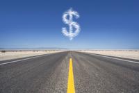 Dollar sign cloud hovering over remote desert road