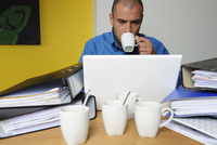 Portrait of young man sitting at desk drinking coffee