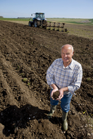 Farmer cupping soil in ploughed field with tractor and plough in background