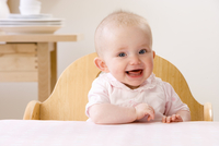 Happy baby girl sitting in high chair