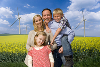 Happy family standing together  in blooming field with wind turbines in background
