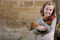 Smiling girl holding pet chicken