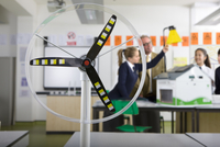 Close up of wind turbine model in science class with teacher and students in school uniforms in background
