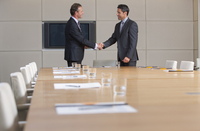 Businessmen in suits shaking hands in conference room