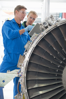 Engineers with digital tablet inspecting engine of passenger jet in hangar